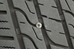 flat-car-tire-wood-screw-imbedded-tread-closeup-horizontal-photo-embedded-40921039